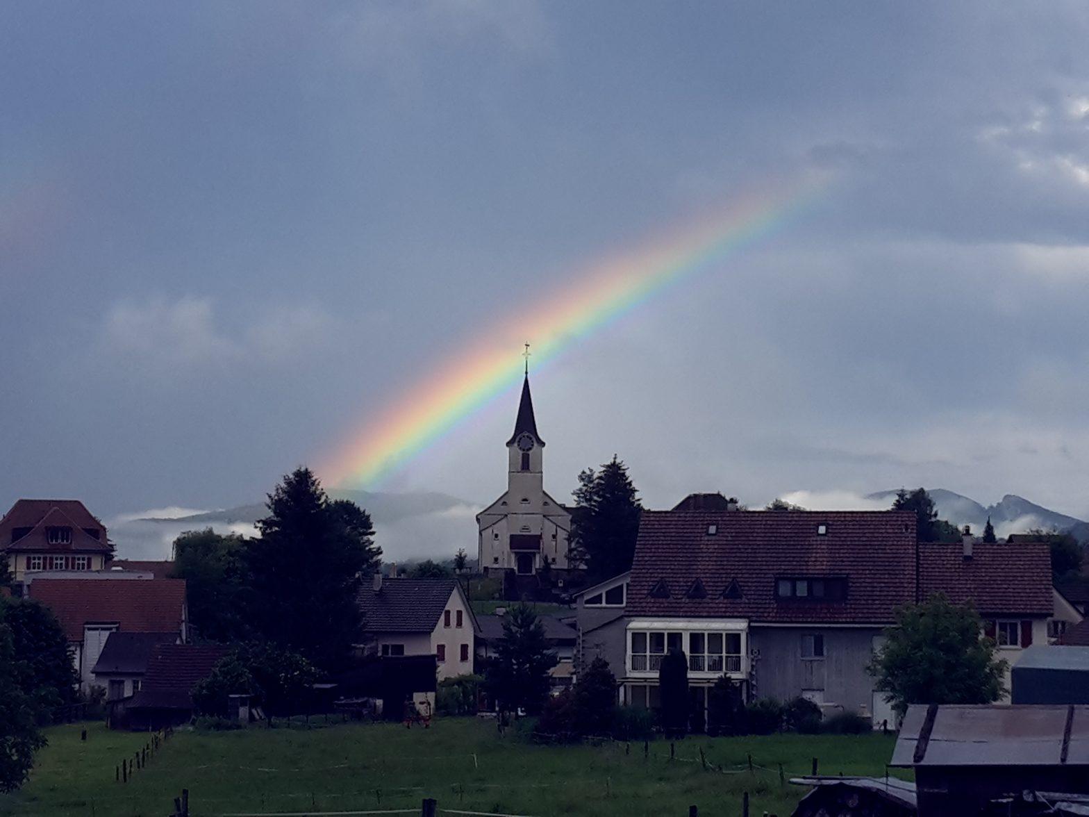 Kirchturm ohne Swisscom Mobilfunkantenne mit Regenbogen